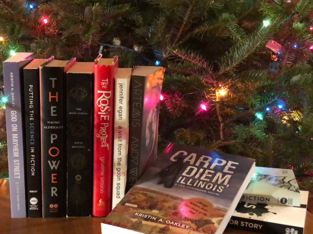 Books stacked by Christmas tree lights