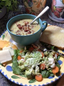 Bowl of bacon leek soup, salad, bread and cheese