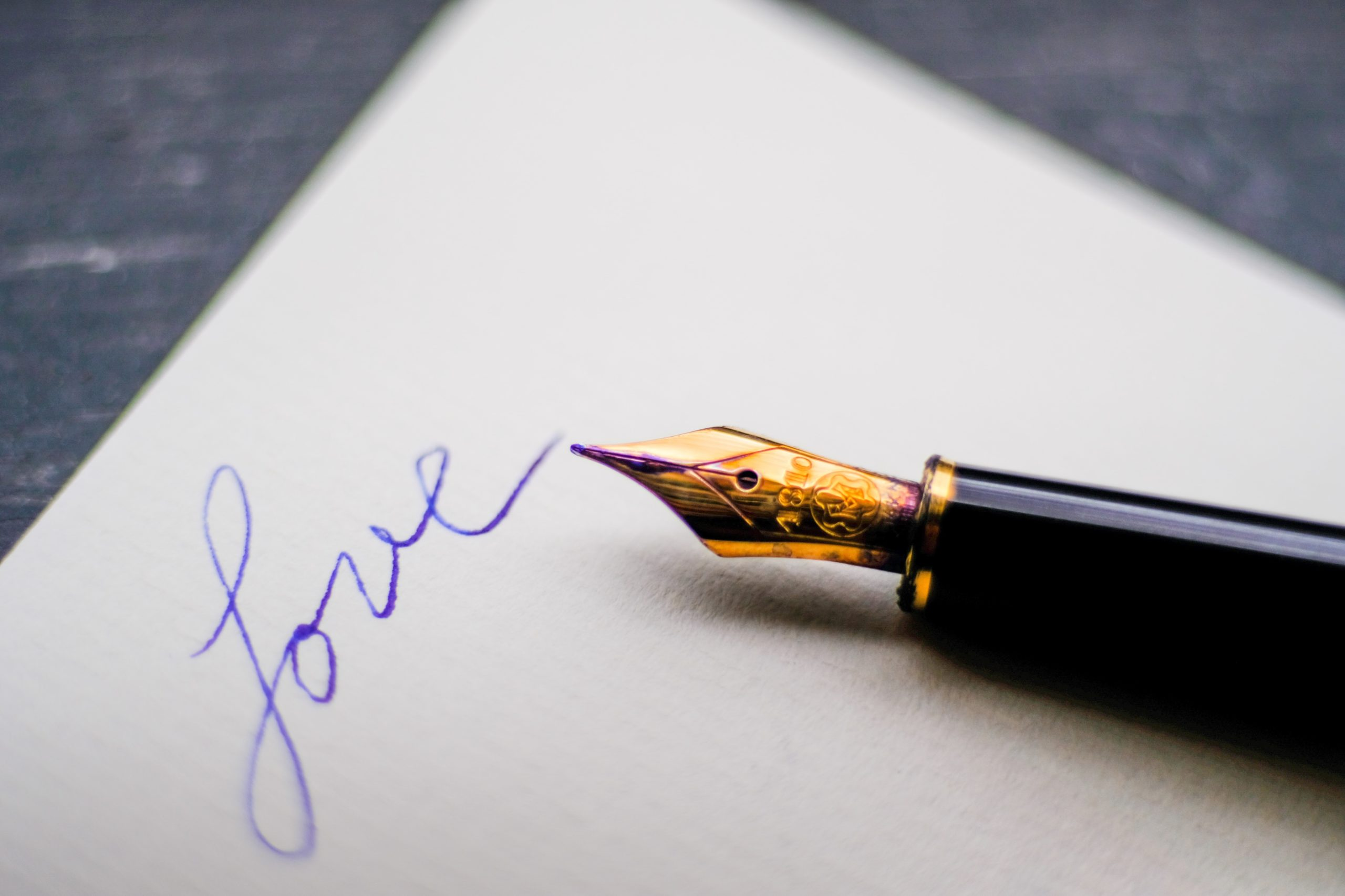 A fountain pen on a piece of paper with the word Love written on it