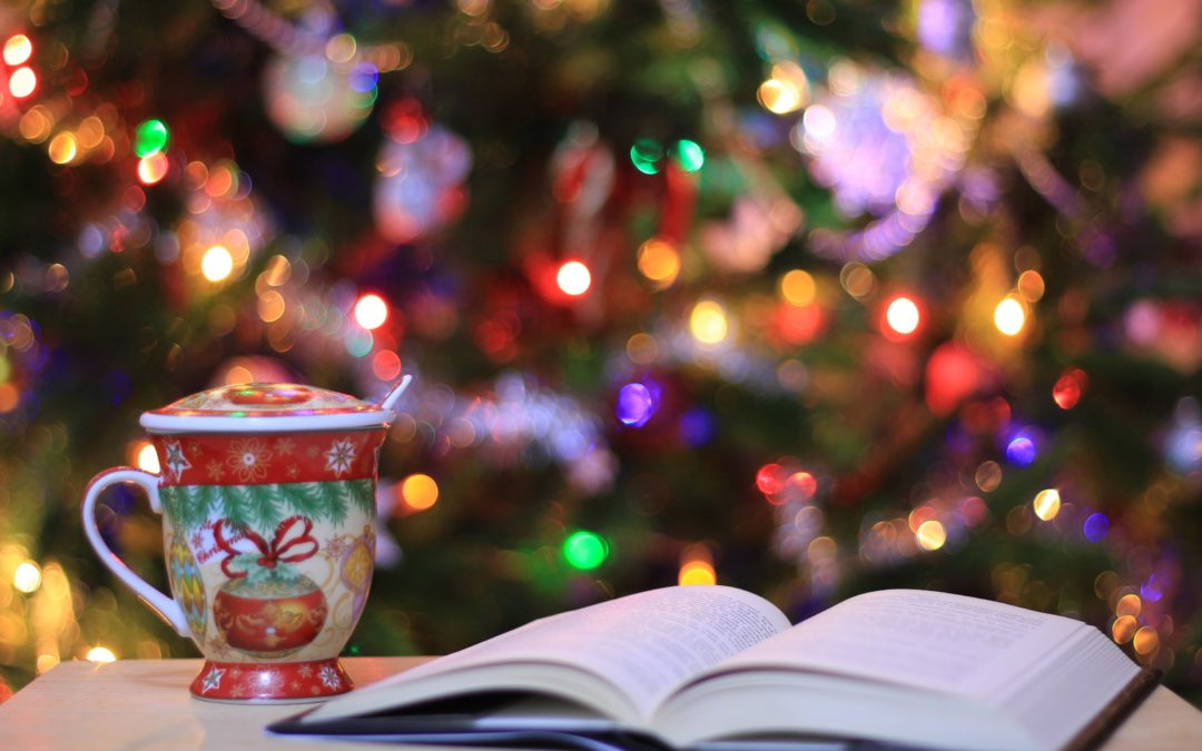 Open book, Christmas mug in front of a lighted Christmas tree