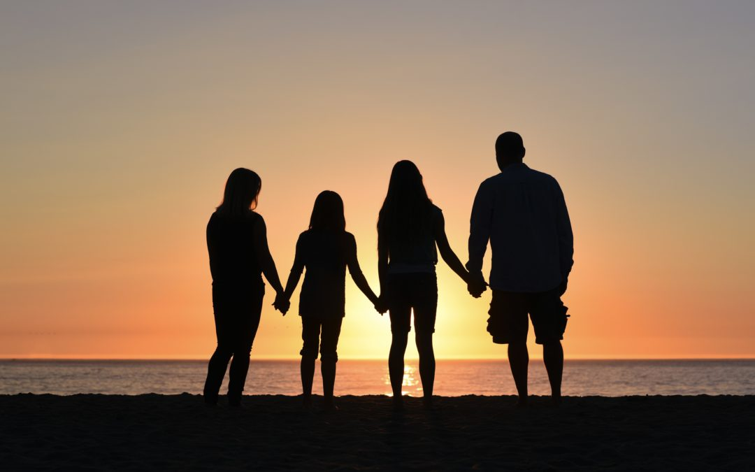 Silhouette of a family of four with sunset