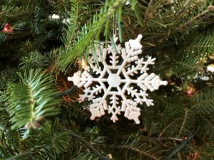 Snowflake ornament hanging in evergreen tree