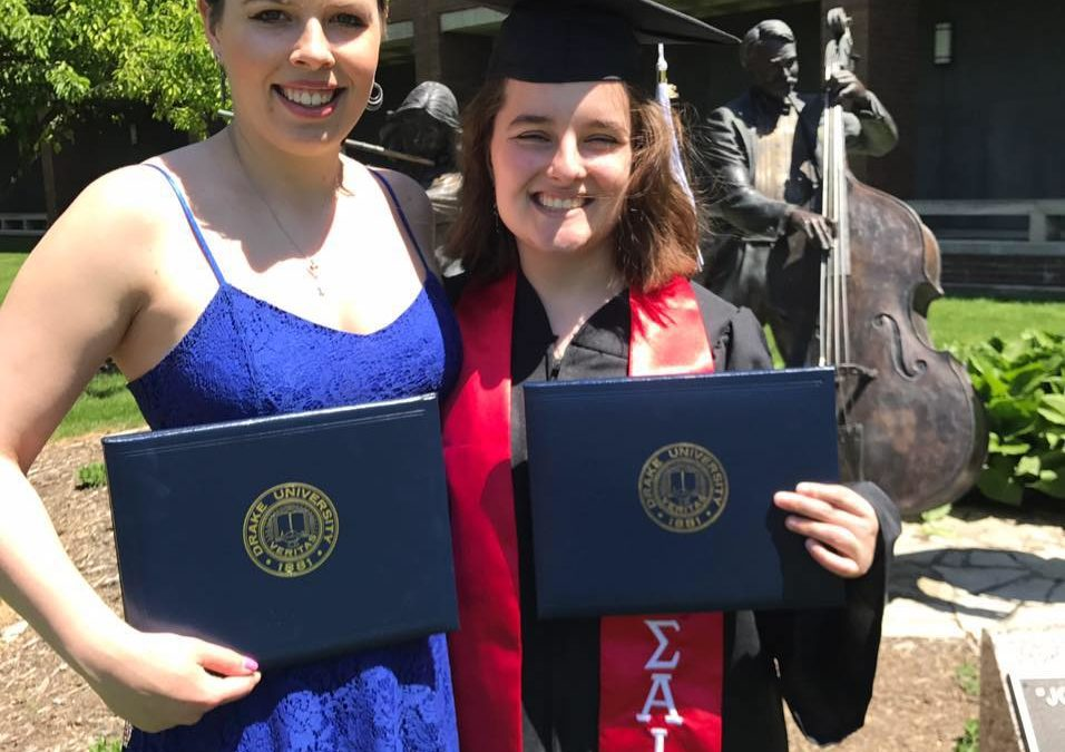 Caitlin and Jessica, in cap in gown,holding their college diplomas on the day Jessica graduates from Drake University