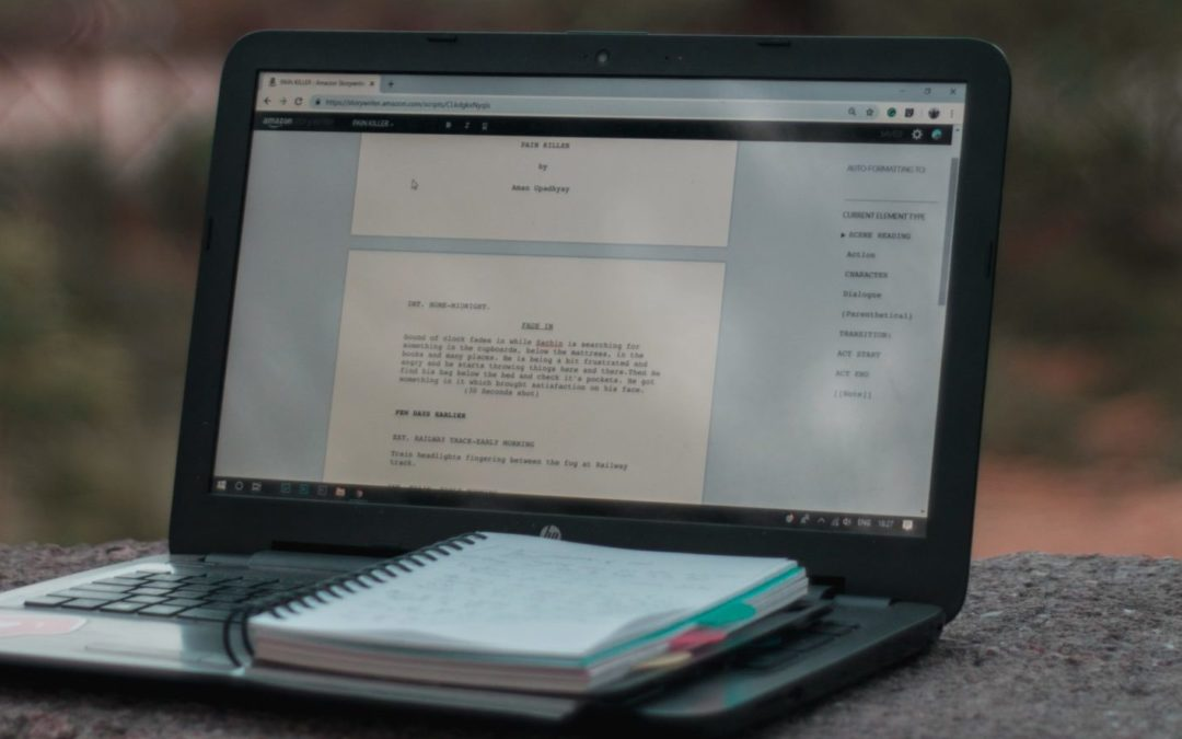 Laptop outside that's open, on the screen is a script, on the keyboard is a notepad