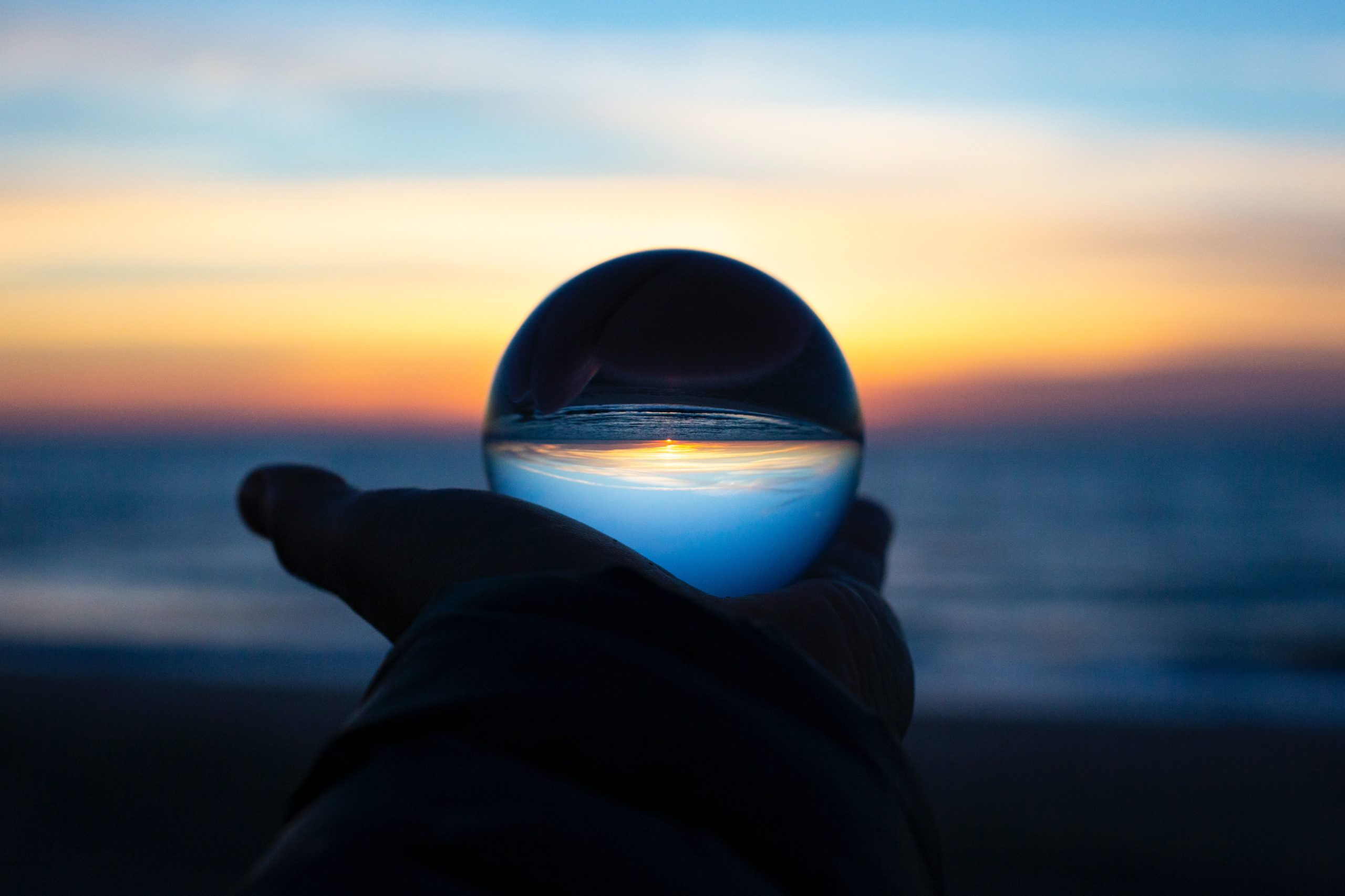 Hand holding a crystal ball which inverts the sunset