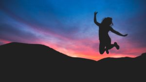 Jumping for joy during a sunset