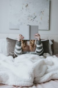 A woman in bed holding a book up while she reads.