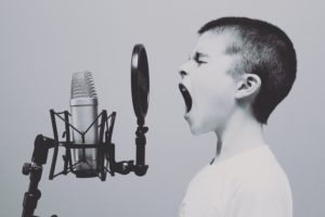 A young boy shouting into an old-fashioned microphone
