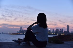 Woman sitting on shore looking across a body of water to a city